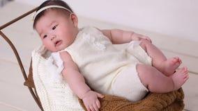 Маленькая азиатская девушка младенец прогулочная коляска шпаргалка в белом костюме акции видеоматериалы