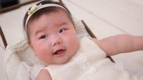 Маленькая азиатская девушка младенец прогулочная коляска шпаргалка в белом костюме сток-видео