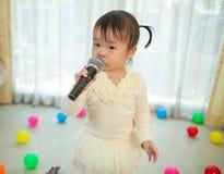 Маленькая азиатская девушка с микрофоном Стоковое Изображение RF