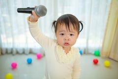 Маленькая азиатская девушка с микрофоном Стоковая Фотография RF
