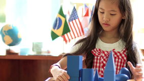 Маленькая азиатская девушка штабелируя блоки montessori акции видеоматериалы
