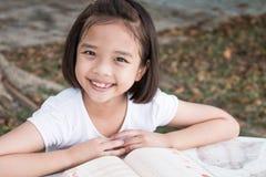 Маленькая азиатская улыбка ребенка и читать книгу стоковые фото