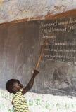 Маленькая африканская девушка в классе работая на тренировках Стоковая Фотография RF