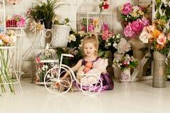 Маленькая белокурая девушка в фиолетовом платье Весна Стоковое фото RF