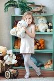 Маленькая белокурая девушка держит полярного медведя в интерьере комнаты ` s детей Стоковые Фотографии RF