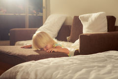 маленькая белокурая девушка стоит близко софа против белых подушек Стоковые Фото