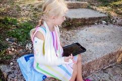 Маленькая белокурая девушка с сломленной рукой стоковые изображения