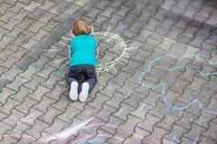 Маленькая белокурая картина мальчика с красочными мел outdoors Стоковое фото RF
