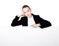 Маленькая бизнес-леди стоя задней и полагаясь на белых пустых афише или плакате, выражает различную, скука Стоковые Изображения