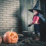 Маленькая ведьма делая волшебное зелье на ноче хеллоуина Тыква Стоковое фото RF