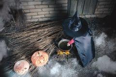 Маленькая ведьма делая волшебное зелье на ноче хеллоуина ужас Стоковые Изображения RF
