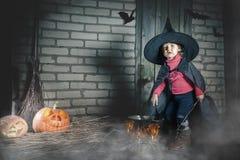 Маленькая ведьма делая волшебное зелье на ноче хеллоуина ужас Стоковое Изображение