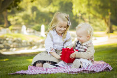 Маленькая девочка дает ее брату младенца подарок валентинки Стоковые Изображения RF