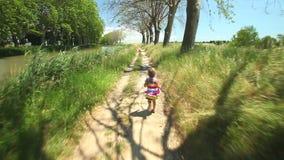Маленькая девочка бежать вдоль следа пути в природе видеоматериал