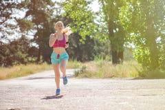 Маленькая девочка бежать в утре в парке города Здоровый фитнес Стоковые Фото