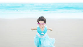Маленькая девочка бежать & играя на голубом пляже стоковые изображения