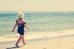 Маленькая девочка бежать и играя на пляже Стоковые Изображения