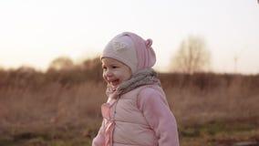 Маленькая девочка бежать и смеясь над на заходе солнца в замедленном движении в розовой одежде акции видеоматериалы