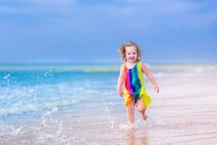 Маленькая девочка бежать на пляже Стоковые Фотографии RF