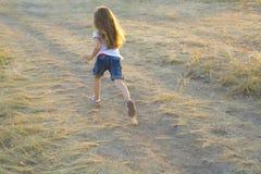 Маленькая девочка бежать на сельской дороге Стоковые Фото