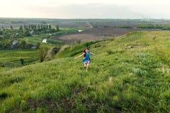 Маленькая девочка бежать на луге Стоковые Фото