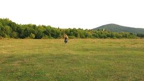 Маленькая девочка бежит прочь Девушка бежит прочь перед камерой Девушка бежать на поле курчавые волосы девушки длиной задний взгл видеоматериал