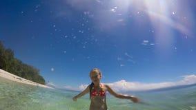 Маленькая девочка брызгая воду в море сток-видео
