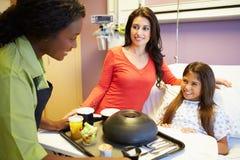 Маленькая девочка будучи послуженным обед в больничной койке Стоковые Фото