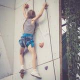 Маленькая девочка взбираясь стена утеса внешняя Стоковое Изображение