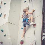 Маленькая девочка взбираясь стена утеса внешняя Стоковые Фотографии RF