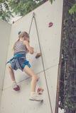 Маленькая девочка взбираясь стена утеса внешняя Стоковые Изображения RF