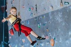Маленькая девочка взбираясь стена утеса крытая Стоковое фото RF
