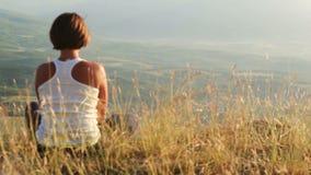 Маленькая девочка встречает солнце на верхней части холма сток-видео