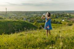 Маленькая девочка выпивает минеральную воду Стоковая Фотография RF