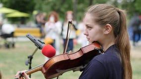 Маленькая девочка выполняет музыкальный состав для passersby, музыкант улицы зарабатывает наличные деньги играя на скрипке, сток-видео