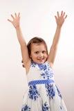 Маленькая девочка вытягивая ее руки вверх стоковое изображение