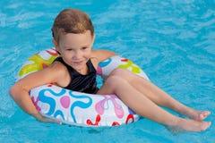 Маленькая девочка в бассейне с резиновым кольцом стоковые фотографии rf