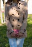 Маленькая девочка в бежевом пальто, голубых джинсах и striped футболке Стоковые Изображения