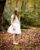 Маленькая девочка в белой балетной пачке самостоятельно в лесе Стоковые Фото