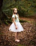 Маленькая девочка в белой балетной пачке самостоятельно в лесе Стоковая Фотография
