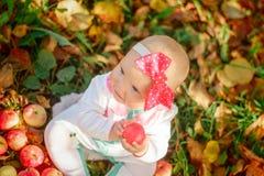 Маленькая девочка в белом костюме с красным усаживанием смычка Стоковое Изображение RF