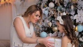 Маленькая девочка в белом платье держит подарок ` s Нового Года видеоматериал