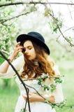 Маленькая девочка в белых платье и черной шляпе в в белом fl стоковое фото