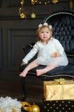 Маленькая девочка в белых платье и circlet цветков сфотографировала для рождественской открытки Стоковое Фото