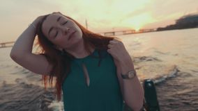 Маленькая девочка в волосах касания платья бирюзы на моторной лодке Заход солнца романтично Улыбка сток-видео