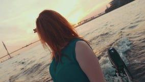 Маленькая девочка в волосах касания платья бирюзы на моторной лодке Посмотрите на заходе солнца романтично видеоматериал