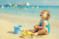 Маленькая девочка в голубом купальнике играет в воде Стоковая Фотография