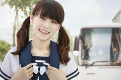 Маленькая девочка в кабелях свиньи в школьной форме коммутируя к школе, смотря камеру стоковые фото