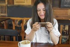Маленькая девочка в кафе, фотоснимках на еде телефона, чашке чаю, кофе, испечет зеленый цвет Стоковые Фотографии RF