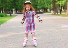 Маленькая девочка в коньках ролика шлема в зеленом парке лета Стоковые Изображения RF